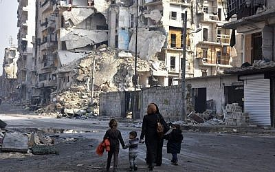 Syrians walk along a damaged street in Aleppo's Tareeq al-Bab neighbourhood on January 18, 2017, a month after government forces retook the northern Syrian city from rebel fighters. (AFP Photo/George Ourfalian)