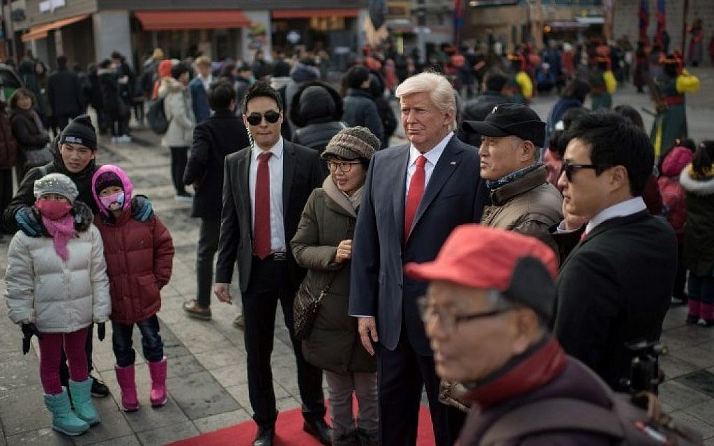 Pedestrians pose with a waxwork figure of US President-elect Donald Trump is prepared to be placed on a street after it was unveilied at the Grevin waxwork museum in Seoul on January 20, 2017. (AFP PHOTO / Ed JONES)