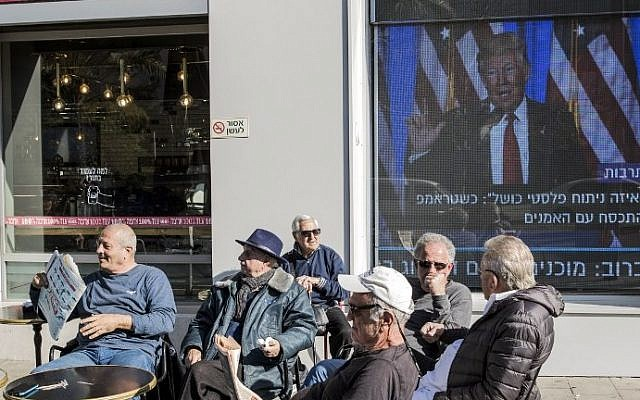 Israelis relax at a cafe in front of giant TV screens playing footage of US President-elect Donald Trump on January 20, 2017 in the coastal city of Tel Aviv prior to his inauguration as the 45th president of the United States. (AFP PHOTO / JACK GUEZ)