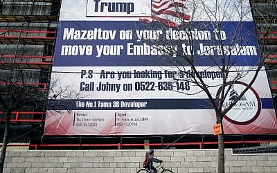 An Israeli child cycles past a giant banner bearing a message of congratulations ('Mazel tov') for incoming US President Donald Trump, covering a building under construction in central Jerusalem on January 20, 2017.  (AFP Photo/Thomas Coex)