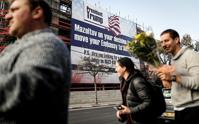 People walk past a giant banner, bearing a message of congratulations (Mazeltov) for US President Donald Trump, covering a building under construction on Jerusalem's Bethlehem Road on January 20, 2017. (AFP Photo/Thomas Coex)