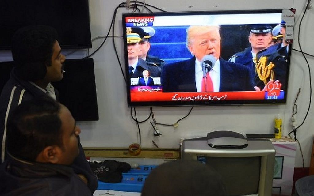 Pakistani residents watch the TV broadcast of the inaugural ceremony of new US President Donald Trump at a market in Karachi, on January 20, 2017. (AFP PHOTO / RIZWAN TABASSUM)