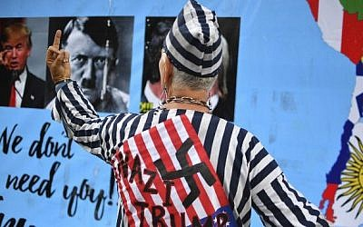 An activist dressed in Nazi concentration camp uniform pictured during a protest against US President Donald Trump in front of the US Embassy in Mexico City on January 20, 2017. (AFP PHOTO / YURI CORTEZ)