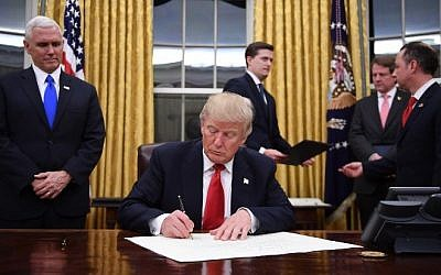 US President Donald Trump signs a confirmation for John Kelly as US Secretary of Homeland Security, as Vice President Mike Pence, left, and White House Chief of Staff Reince Priebus, right, look on, in the Oval Office of the White House in Washington, DC, January 20, 2017. AFP/ JIM WATSON)