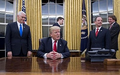 US President Donald Trump, center, speaks to the press at his desk in the Oval Office of the White House  in Washington, DC, January 20, 2017. (AFP PHOTO / JIM WATSON)