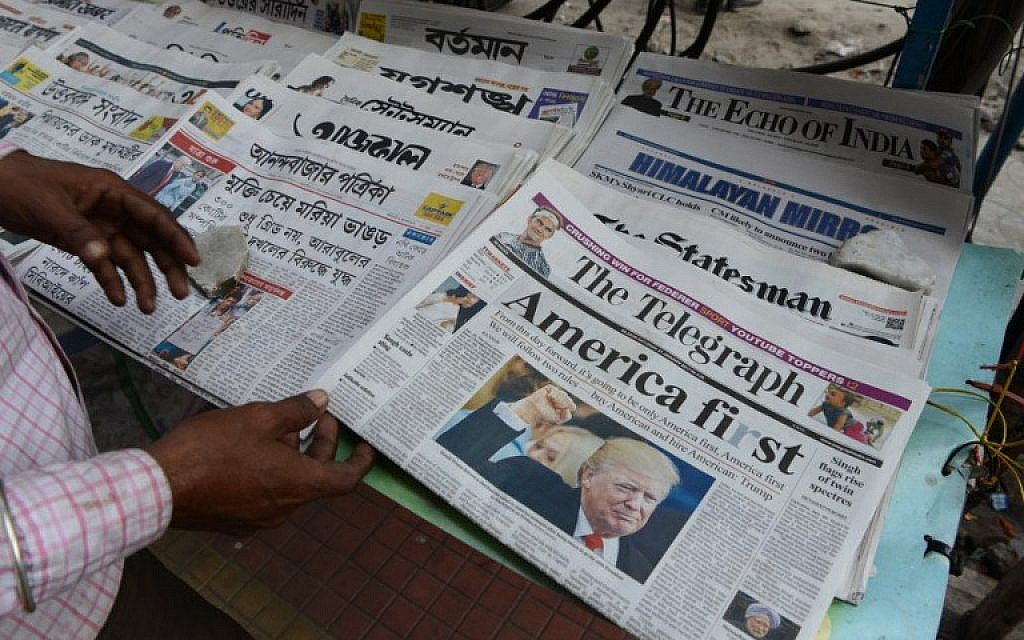 An Indian man reads a newspaper carrying front page news of the inauguration of US President Donald Trump, at a newspaper stand in Siliguri on January 21,2017. (AFP PHOTO / Diptendu DUTTA)