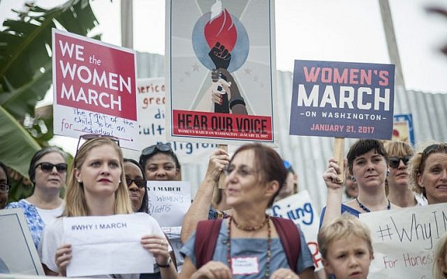People take part in the Women's March in front of the USA embassy in Accra, Ghana on January 21, 2017. (AFP PHOTO/CRISTINA ALDEHUELA)