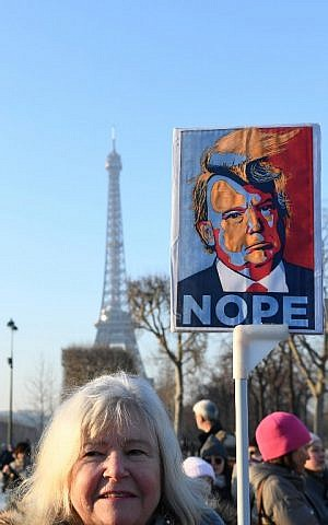 A demonstrator carries a sign during a rally in front of the Eiffel Tower in Paris in solidarity with the Women's March in Washington and many other cities on January 21, 2017 (AFP PHOTO/ALAIN JOCARD)