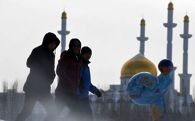 Men walk along a street, with the Nur-Astana mosque seen in the background, in Astana, Kazakhstan on January 22, 2017. (Kirill Kudryavtsev/AFP)