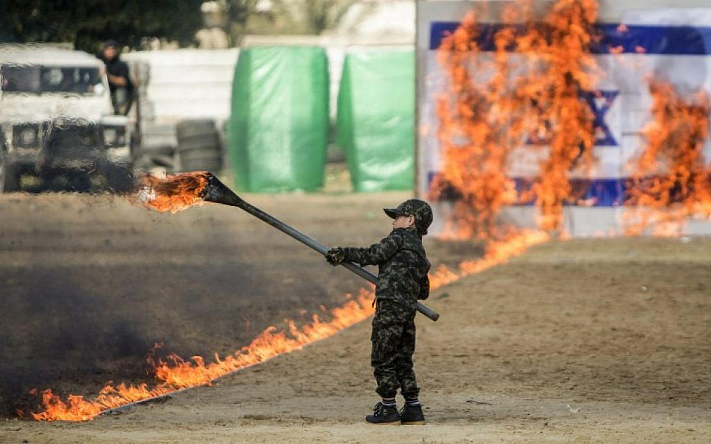 A Palestinian boy sets fire to a line of flames leading to an Israeli flag during a graduation ceremony for Hamas security forces in Gaza City on January 22, 2017. (AFP /MAHMUD HAMS)