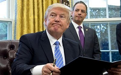 US President Donald Trump signs an executive order as Chief of Staff Reince Priebus looks on in the Oval Office of the White House in Washington, DC, January 23, 2017. (AFP PHOTO / SAUL LOEB)