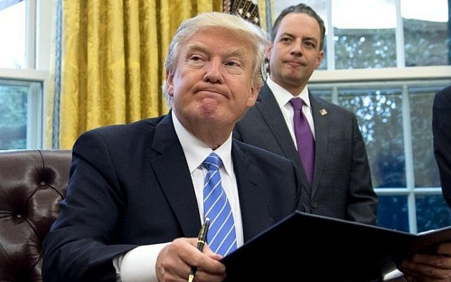 US President Donald Trump signs an executive order as then chief of ftaff Reince Priebus looks on in the Oval Office of the White House, on January 23, 2017. (AFP/Saul Loeb)
