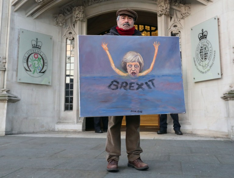 Satirical artist Kaya Mar poses with a Brexit-themed artwork depicting British Prime Minister Theresa May, as he stands outside the Supreme Court, opposite the Houses of Parliament, in central London on January 24, 2017. (AFP PHOTO / POOL / Jonathan Brady)