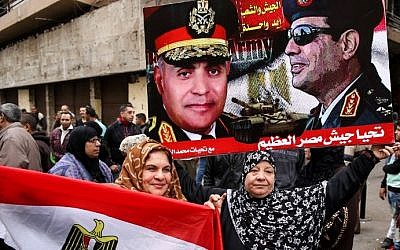 Egyptian women hold their national flag and a poster bearing portraits of President Abdel Fattah al-Sissi and Defense Minister Sedki Sobhi, as they celebrate the sixth anniversary of the 2011 uprising that overthrew former Egyptian president Hosni Mubarak in Cairo's Tahrir Square on January 25, 2017. AFP/STRINGER)