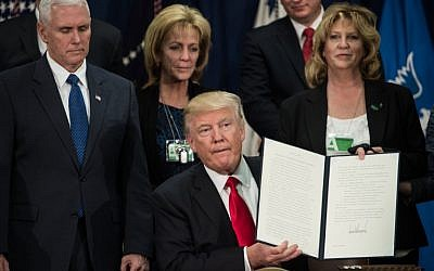 US President Donald Trump holds up an executive order to start the Mexico border wall project at the Department of Homeland Security facility in Washington, DC, on January 25, 2017. (AFP/Nicholas Kamm)