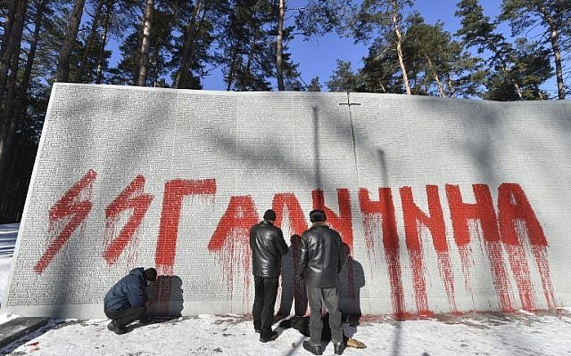 Employees examine Nazi SS graffiti written on a wall dedicated to Polish officers at the Bykovnia Memorial Cemetery, near to Kiev, on January 26, 2017. (AFP PHOTO / Sergei SUPINSKY)