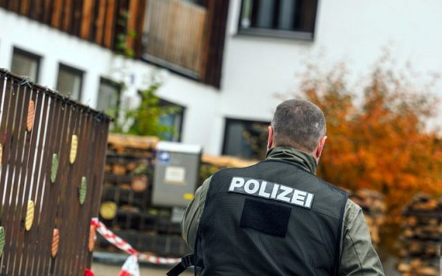 This photo taken on October 19, 2016 shows a policeman pictured in Georgensgmuend, southern Germany, in front of a house of a member of the so-called Reichsbuerger movement. (AFP/dpa/Nicolas Armer)