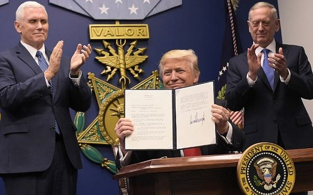 US President Donald Trump holds up an executive action on rebuilding the armed forces after signing it on January 27, 2017 at the Pentagon in Washington, DC. Looking on are US Vice President Mike Pence (L) and US Defense Secretary James Mattis. (AFP PHOTO/MANDEL NGAN)