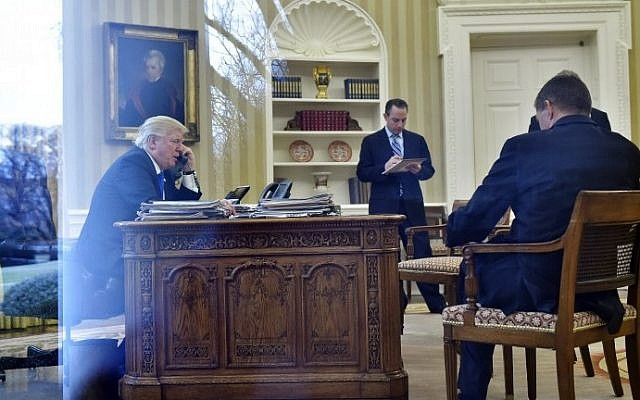 US President Donald Trump speaks on the phone with Germany's Chancellor Angela Merkel from the Oval Office of the White House on January 28, 2017 in Washington, DC.  (AFP PHOTO / MANDEL NGAN)