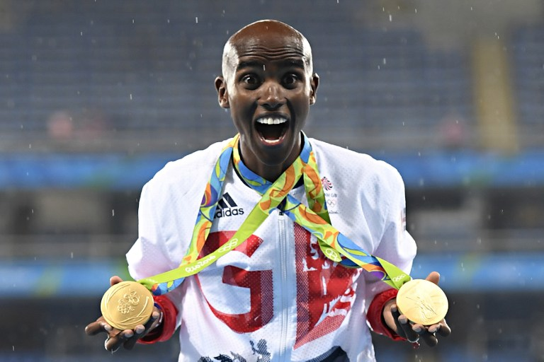 Gold medallist Britain's Mo Farah celebrates near the podium for the Men's 5000m during the athletics event at the Rio 2016 Olympic Games at the Olympic Stadium in Rio de Janeiro on August 20, 2016. (AFP PHOTO / Eric FEFERBERG)