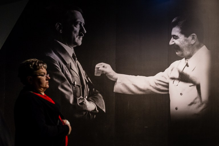 A woman passes by photographs of Adolf Hitler and Joseph Stalin on January 29, 2017 at the permanent exhibition of Museum of Second World War open days ahead of the official opening planned for the end of February in Gdansk, Poland. (AFP PHOTO / Wojtek RADWANSKI)