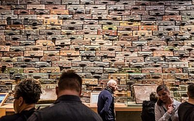People look at piled up suitcases on January 29, 2017 as part of the permanent exhibition of Museum of Second World War opened for two days ahead of the official opening planned for the end of February in Gdansk, Poland. (AFP PHOTO / Wojtek RADWANSKI)
