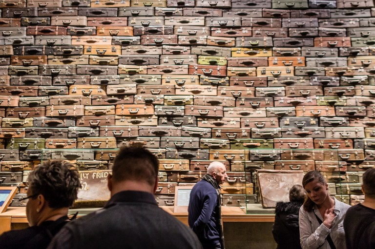 People look at piled up suitcases on January 29, 2017 as part of the permanent exhibition of Museum of Second World War opened for two days ahead the official opening planned for the end of February in Gdansk, Poland. (AFP PHOTO / Wojtek RADWANSKI)
