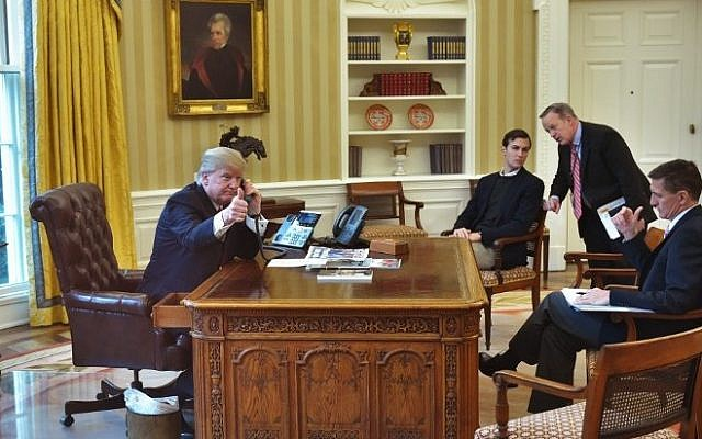 US President Donald Trump seen through an Oval Office window gives a thumbs up as he speaks on the phone to King Salman of Saudi Arabia in the Oval Office of the White House on January 29, 2017 in Washington, DC. (AFP PHOTO / MANDEL NGAN)