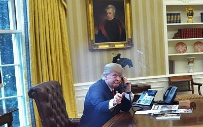 US President Donald Trump, left, seen through an Oval Office window, speaks on the phone to King Salman of Saudi Arabia in the Oval Office of the White House on January 29, 2017 in Washington, DC. (AFP/ Mandel Ngan)
