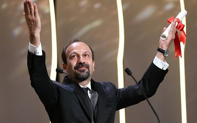 "Iranian director Asghar Farhadi celebrating on stage after being awarded with the Best Screenplay prize for the film ""The Salesman (Forushande) during the closing ceremony of the 69th Cannes Film Festival in Cannes, southern France, May 22, 2016. (AFP PHOTO / Valery HACHE)"