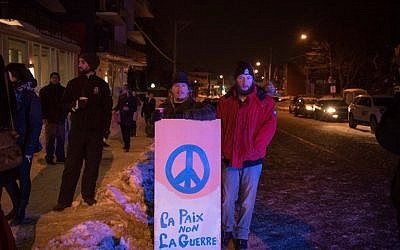 People stand with a peace sign near the Québec City Islamic cultural center after a shooting in the mosque on Sainte-Foy Street in Quebec city on January 29, 2017. (AFP/Alice Chiche)
