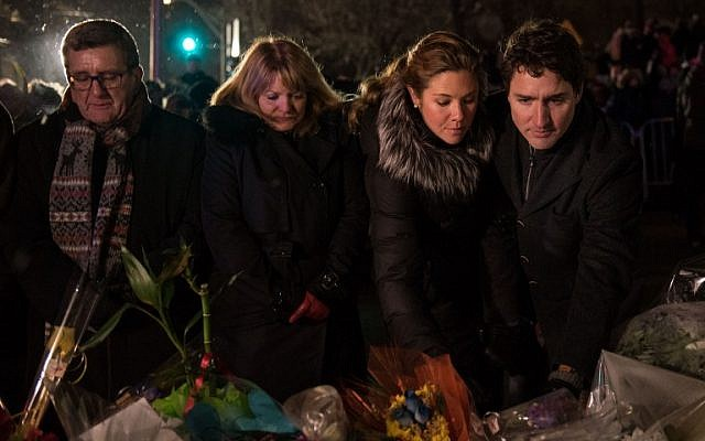 (L-R) Quebec city mayor Regis Labeaume, his wife, Sophie Gregoire (Justin Trudeau's wife) and Canadian prime minister Justin Trudeau lay flowers near the Islamic Cultural Center in Quebec City, Canada on January 30, 2017.(AFP PHOTO / Alice Chiche)