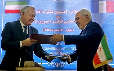 French Foreign Minister Jean-Marc Ayrault (L) and Iranian Foreign Minister Mohammad Javad Zarif exchange documents after signing economic agreements in Tehran on January 31, 2017.(AFP PHOTO / ATTA KENARE)