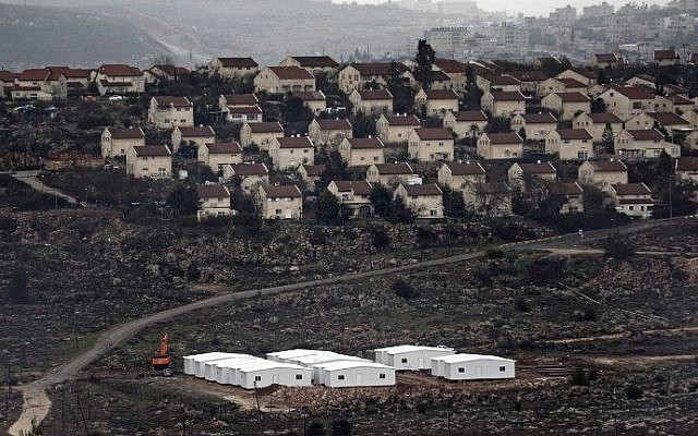 New prefabricated homes are seen under construction in the West Bank between the Israeli outpost of Amona and the settlement of Ofra (background), north of Ramallah, on January 31, 2017. (AFP/Thomas Coex)