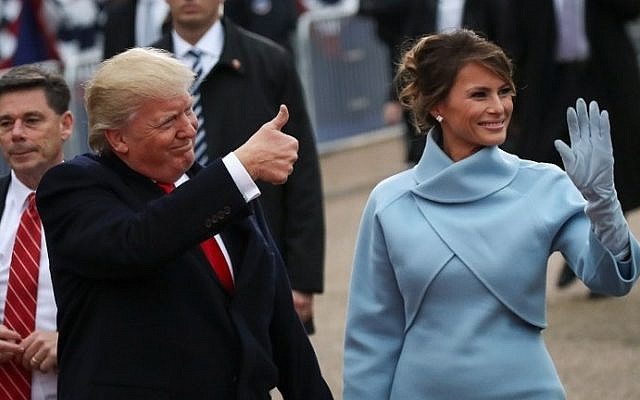 US President Donald Trump (L) waves to supporters as he walks the parade route with first lady Melania Trump during the Inaugural Parade on January 20, 2017 in Washington, DC. (Drew Angerer/Getty Images/AFP)