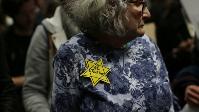 A woman wears a pin during a rally against Muslim immigration ban at San Francisco International Airport on January 28, 2017 in San Francisco, California. (Stephen Lam/Getty Images/AFP)