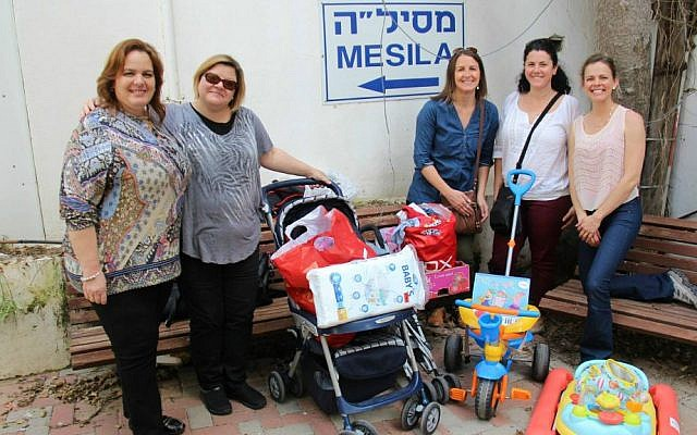 Julie Fisher (second from left) and her Diplomatic Spouses of Israel co-president Rocio Gonzales of Peru and other diplomatic spouses deliver donations to Mesila, and aid and information center for refugees and migrant workers in Tel Aviv. (Mesila)