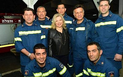 A Cypriot firefighter, standing to the right of Prime Minister Benjamin Netanyahu's wife Sara, is wearing a chief inspector's jacket with three stars, when his rank is apparently only inspector. (Cobi Gidon / GPO)