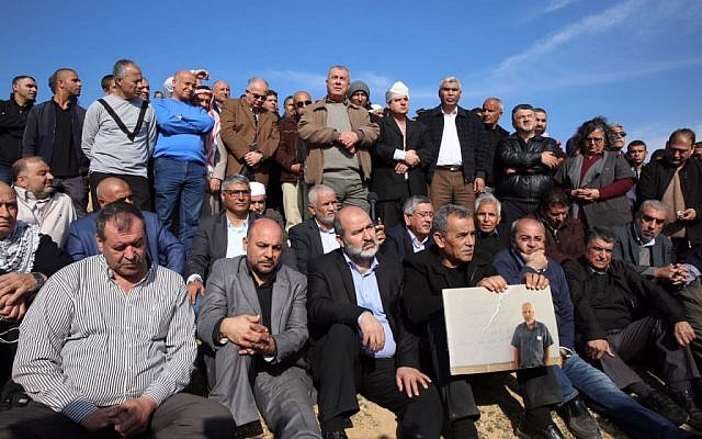MK Ayman Odeh (back row, with white bandage on head) of the Joint List and other Arab Israeli leaders stand at the scene of fatal clashes in the Bedouin village of Umm al-Hiran, on Wednesday, January 18, 2017 (courtesy)