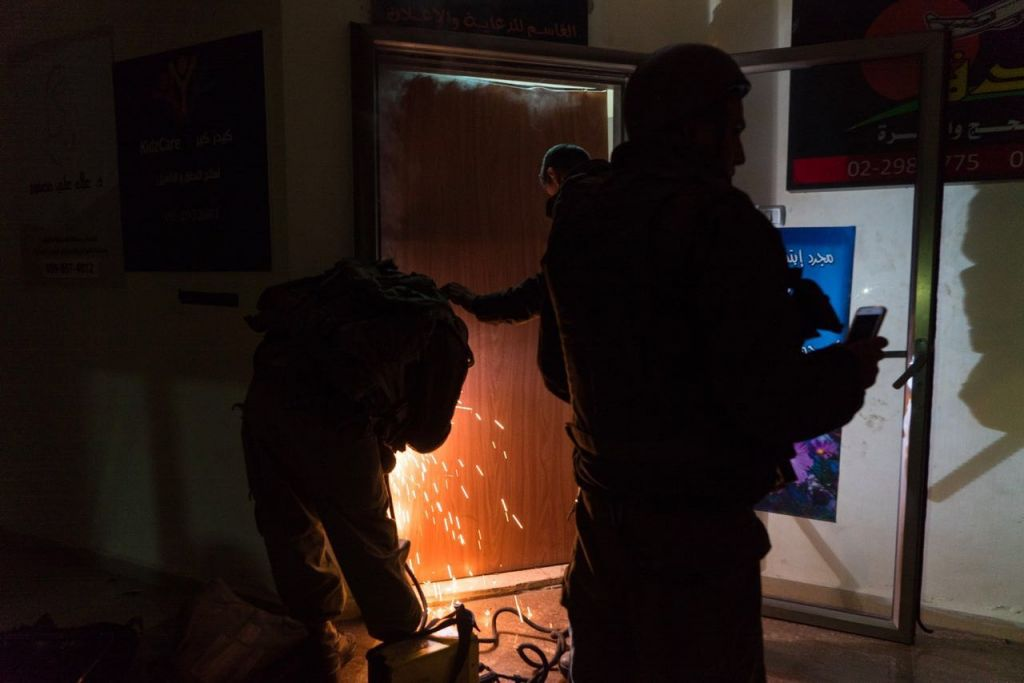 IDF soldiers weld shut a printing shop suspected of being used to publish 'inciting' materials in Ramllah on January 30, 2017. (IDF Spokesperson's Unit)