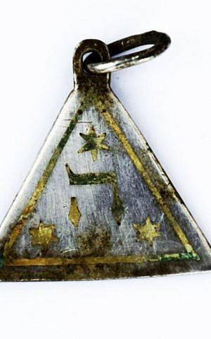 The reverse of a pendant showing the Hebrew letter symbolizing God's name found at the site of the Nazi-operated Sobibor death camp. (Yoram Haimi/Israel Antiquities Authority)