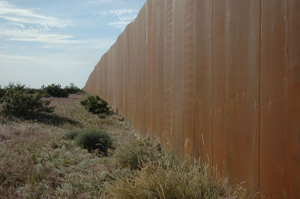 The Wall, US border, separating Mexico from the US, looking east, along Highway 2, Sonora Desert, Mexican side (CC BY Wonderlane, Flickr)