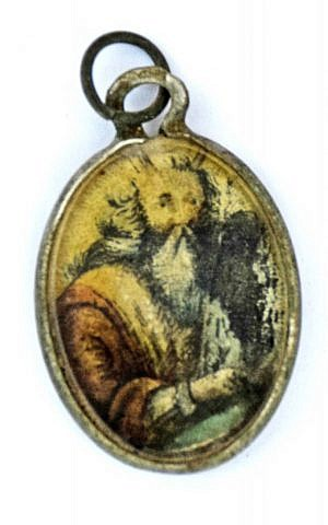 A metal locket covered with glass with the image of Moses holding the Ten Commandments painted on it, found at the site of the former Nazi death camp of Sobibor. (Yoram Haimi/Israel Antiquities Authority)