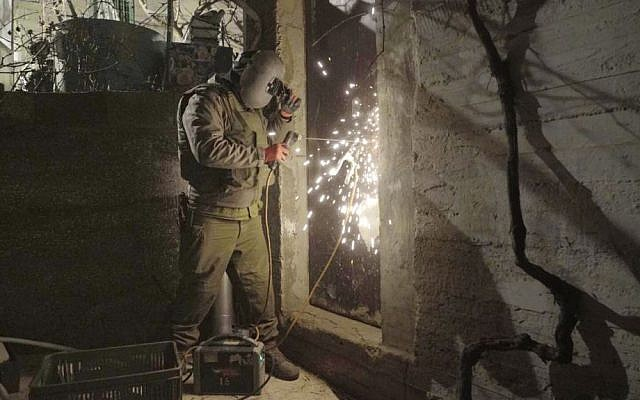 An IDF soldier welds shut a workshop suspected of being used to manufacture illegal guns in Hebron on January 30, 2017. (IDF Spokesperson's Unit)