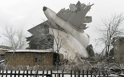 The tail of a crashed Turkish Boeing 747 cargo plane lies at a residential area outside Bishkek, Kyrgyzstan Monday, Jan. 16, 2017. The cargo plane crashed Monday morning, killing people in the residential area adjacent to the Manas airport as well as those on the plane. (AP Photo/Vladimir Voronin)