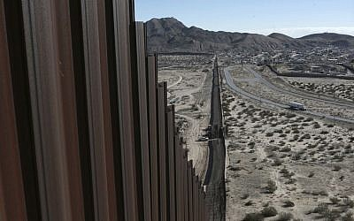 A truck drives near the Mexico-US border fence, on the Mexican side, separating the towns of Anapra, Mexico and Sunland Park, New Mexico, Wednesday, Jan. 25, 2017. (AP/Christian Torres)