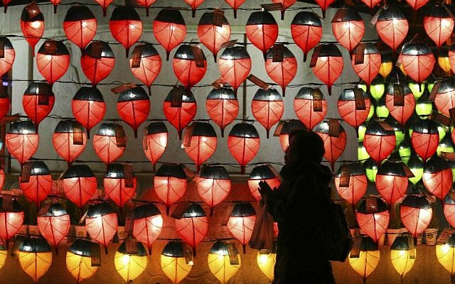 A woman prays in front of lanterns to celebrate the new year at Chogye Buddhist temple in Seoul, South Korea, Saturday, Dec. 31, 2016. (AP Photo/Ahn Young-joon)