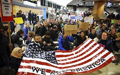 "Demonstrators sit down in the concourse and hold a sign that reads ""We are America,"" as more than 1,000 people gather at Seattle-Tacoma International Airport, to protest President Donald Trump's order that restricts immigration to the US, Saturday, January 28, 2017, in Seattle. (Genna Martin/seattlepi.com via AP)"