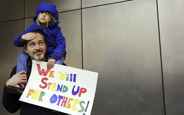 Matt Sernett holds his daughter Wade, 5, atop his shoulders, as more than 1,000 people gather at Seattle-Tacoma International Airport, to protest President Donald Trump's order that restricts immigration to the US, Saturday, Jan. 28, 2017, in Seattle. (Genna Martin/seattlepi.com via AP)