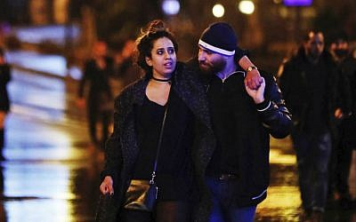Young people leave the scene of a shooting attack in Istanbul, early Sunday, Jan. 1, 2017. (AP Photo/Halit Onur Sandal)